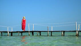 Two frames in video. Beautiful woman walking down pier in long red dress. Phu Quoc Island. The woman enjoys views of the. Two frames in video. On this video you stock video footage