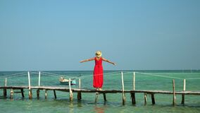 Two frames in video. Beautiful woman walking down pier in long red dress. Phu Quoc Island. The woman the traveler walks. Two frames in video. On this video you stock video footage