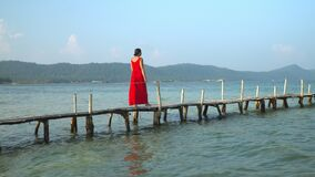 Two frames in video. Phu Quoc Island. The woman goes on a wooden pier to the sea. Close up of legs. The woman barefoot. Two frames in video. On this video you stock video
