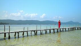 Two frames in video. Beautiful woman walking down pier in long red dress. Phu Quoc Island. The woman enjoys views of the. Two frames in video. On this video you stock video