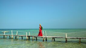 Two frames in video. Beautiful woman walking down pier in long red dress. Phu Quoc Island. The woman the traveler walks. Two frames in video. On this video you stock video