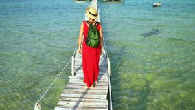 Two frames in video. The woman in a long red dress walks on a pier along blue water. Phu Quoc Island. The woman the. Two frames in video. On this video you can stock video footage