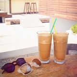 Two frappes and sunglasses on table. Two frappes and sunglasses on vintage table Royalty Free Stock Photos