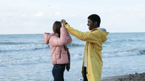 Friends having fun and enjoy together on the beach. Two free cultural person of trendy black male and attractive european female. Lovers keep each other, clap stock video footage