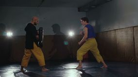 Two free fighters training kicks and receptions in the gym. Slowly.  stock footage