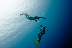 Two freedivers have fun in the depth Royalty Free Stock Photography