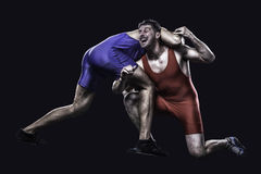 Two freestyle wrestlers in action. Two freestyle wrestlers in red and blue wrestling uniform isolated on black background Stock Images