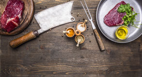 Two fresh beef steaks with spices, butcher knife and fork the meat, place for text Royalty Free Stock Photography