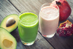 Two fresh blended fruit smoothies. Made with avocado, pomegranate royalty free stock photography