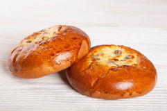 Two fresh buns. Two fresh homemade buns with cottage cheese and raisins on a wooden background Royalty Free Stock Photo