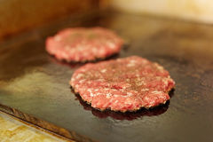Two fresh burger patties frying on a grill Stock Photo