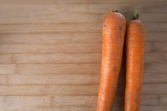 Two fresh carrots on a wooden board Royalty Free Stock Photos