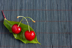 Two fresh cherries and a leaf on bamboo tablecloth Royalty Free Stock Image