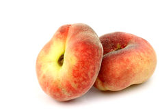 Two fresh colorful flat peaches (donut peaches) Stock Images