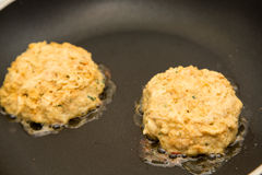 Two Fresh Crab Cakes Cooking in Oil Royalty Free Stock Images