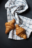 Two fresh croissant lying on a blackboard. Also, there is twisted linen towel. Stock Images