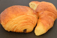 Two fresh croissants. On a black background Stock Photos