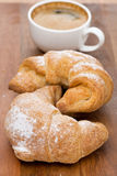 Two fresh croissants and coffee on a wooden background Stock Photo