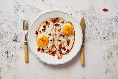 Two fresh fried eggs with crunchy crisp bacon and chive served on rustic plate royalty free stock photography