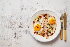 Two fresh fried eggs with crunchy crisp bacon and chive served on rustic plate stock photos