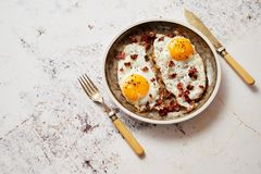 Two fresh fried eggs with crunchy crisp bacon served on rustic plate royalty free stock photo