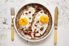 Two fresh fried eggs with crunchy crisp bacon served on rustic plate royalty free stock photos