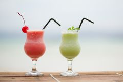 Two fresh fruit juices on a beach Royalty Free Stock Image