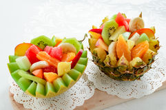 Two fresh fruit salad in handmade melon and pineapple bowl. Royalty Free Stock Images