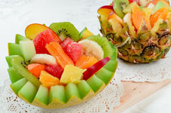 Two fresh fruit salad in handmade melon and pineapple bowl. Stock Photos