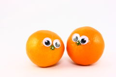 Two Fresh Fruits With Wiggly Eyes. Two fresh clementine fruits decorated with wiggly plastic eyes Royalty Free Stock Photography