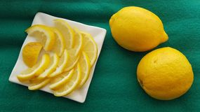 Lemons on white plate on green background stock photos
