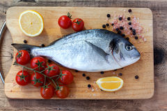 Two fresh gilt-head bream fish on cutting board. Two fresh gilt-head bream fish with lemon, cherry tomato, pink salt and pepper on cutting board Stock Image
