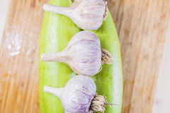 Two fresh green zucchini 3 head of garlic. Two fresh green zucchini and three heads of garlic lying on top of them on a wooden brown cutting boardcooking Royalty Free Stock Image