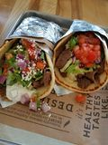 Two Greek Gyro Sandwiches. Two fresh Gyro sandwiches wrapped up with tomatoes, meat, onion, lettuce, feta cheese, in a pita with foil on a tray royalty free stock photography