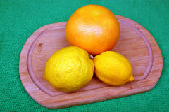Two fresh lemons and orange on a wooden board Stock Images