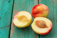 Two fresh nectarines, whole and split with stone, on vintage tur Royalty Free Stock Photo