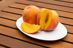 Two fresh peaches on while oval plate Royalty Free Stock Image