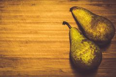 Two fresh pears not peeled on a wooden board. Vitamin, healthy food. stock image