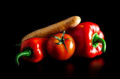 Two fresh peppers, tomatoes and carrots on a black background. Royalty Free Stock Photo