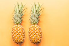 Two fresh pineapples lying on orange background. Top view. Flat lay concept. Place for text royalty free stock photo
