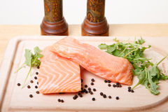 Salmon Fillets on Board with Peppercorns and Arugula Stock Image