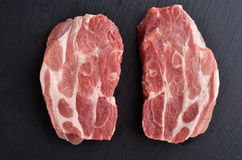 Two fresh raw boneless pork shoulder butt slices. On black stone background. Top view Royalty Free Stock Photo