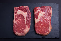 Two fresh raw marble meat, black Angus ribeye steak on a dark stone background.  Royalty Free Stock Images