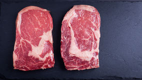 Two fresh raw marble meat, black Angus ribeye steak on a dark stone background. stock image