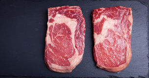 Two fresh raw marble meat, black Angus ribeye steak on a dark stone background. With copy space Stock Photography