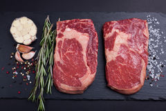 Two fresh raw marble meat, black Angus ribeye steak with spices on a dark stone background.  Royalty Free Stock Photos