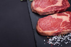 Two fresh raw marble meat, black Angus ribeye steak with spices on a dark stone background. With copy space Stock Photography