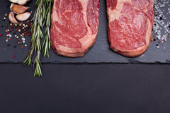 Two fresh raw marble meat, black Angus ribeye steak with spices on a dark stone background. With copy space Stock Photos
