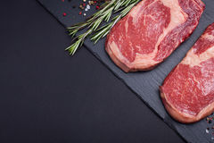 Two fresh raw marble meat, black Angus ribeye steak with spices on a dark stone background. With copy space Royalty Free Stock Images