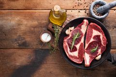 Two fresh raw marble meat, black Angus ribeye steak with spices in iron pan on a old rustic table. Raw beef on a wooden background. Top view with copy space Royalty Free Stock Images
